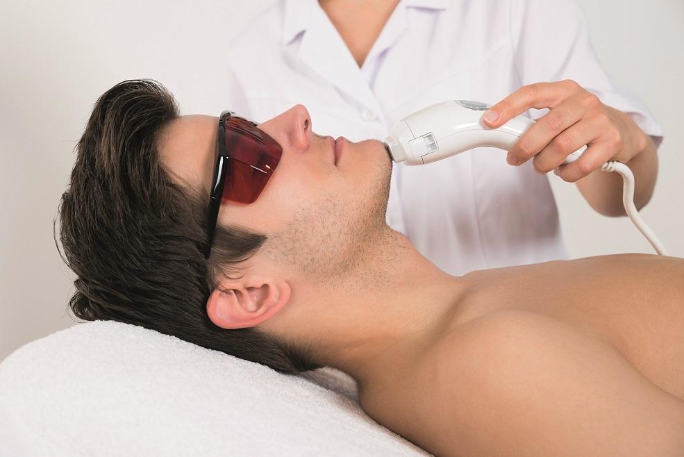 Médico aplicando depilação a laser em barba de paciente homem branco